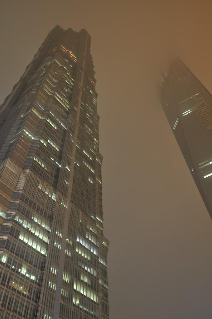 左側、電球色の灯りが点いているフロアが上海金茂君悦大酒店54階のフロント(ビルは88階420m)。右側は建設中の上海環球金融中心(101階492m)。